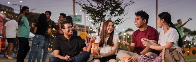 Students sitting together eating popcorn at Adelaide Fringe Festival
