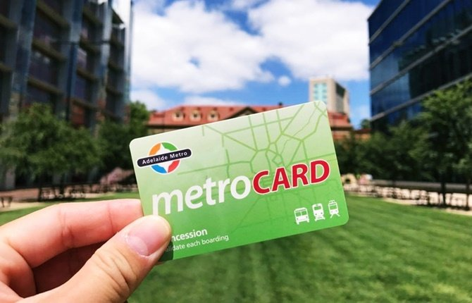 Hands holding green Adelaide Metro concession card infront of buildings