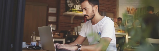 Male student sitting infront of laptop in a cafe
