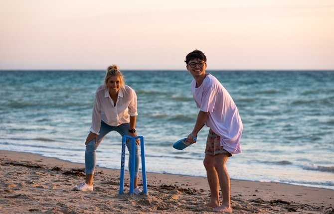Female student and male student playing cricket on the beach