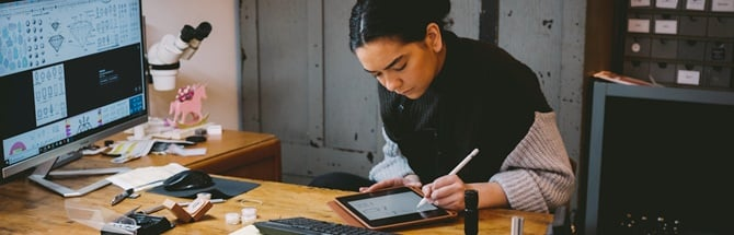 Female student sitting infront of a computer and designing on an iPad