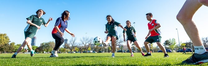 School students kicking soccer ball in park