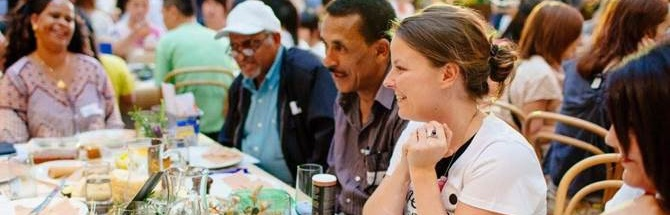 A multicultural group of people sitting around a dining table and talking