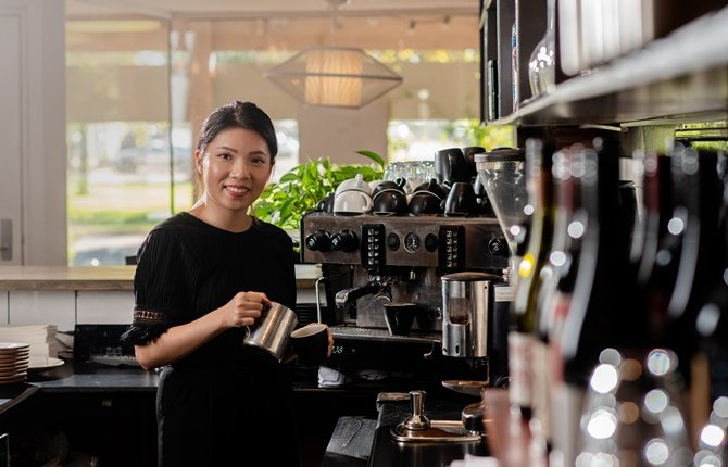 Female student standing infront of a coffee machine making coffee