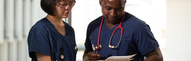 Female and male student in nursing uniform looking at a chart